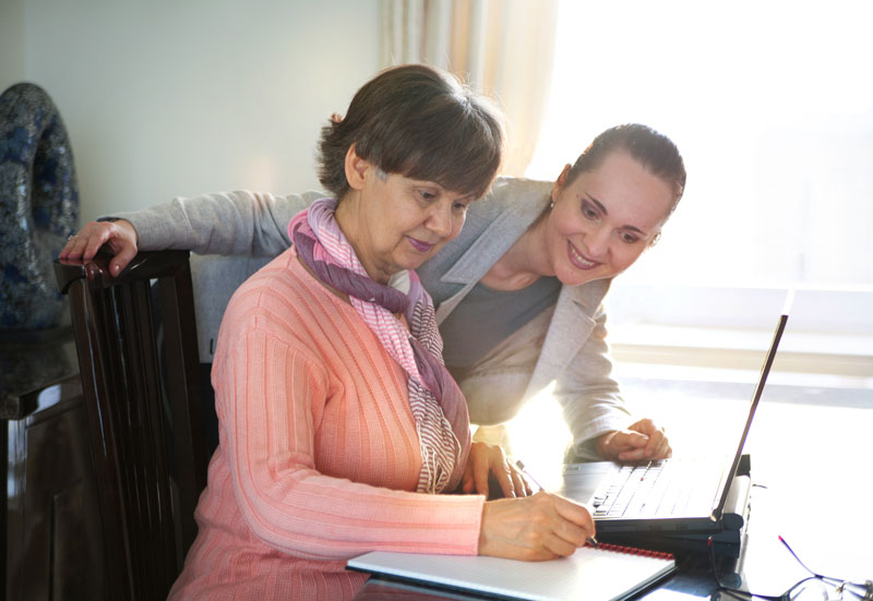 Photo of woman helping older woman on the computer